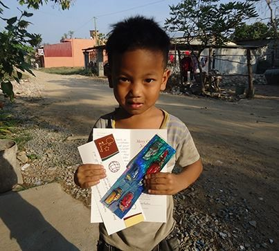 ChildCARE Plus sponsored child with his Christmas card from his sponsor