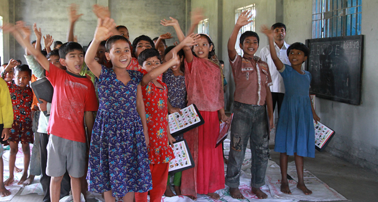 Pre-primary school children in Bangladesh wave to friends