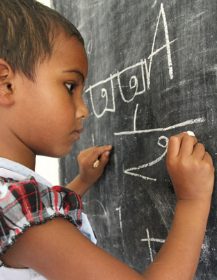 A young girl in Bangladesh is working hard at the blackboard