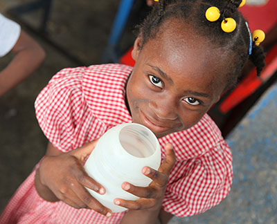 A young girl holds a cup of clean water