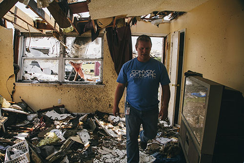 A Convoy of Hope worker walks through a damaged house from the Tornado