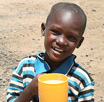 A boy holds up his cup from the feeding program in Kenya