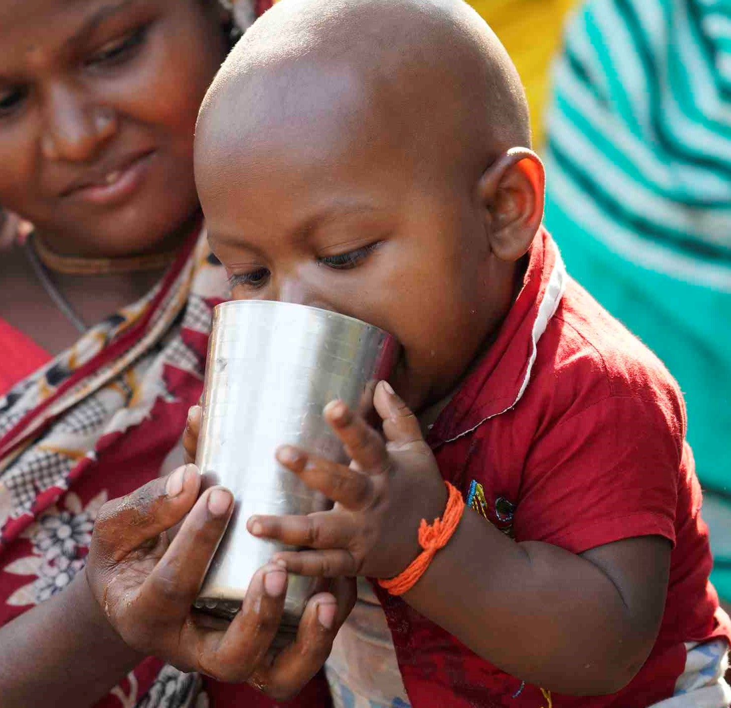 Child in Bangladesh drinking cup of water