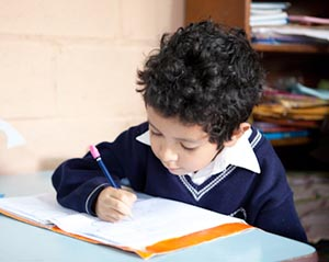 Guatemala - a boy works in his notebook at school