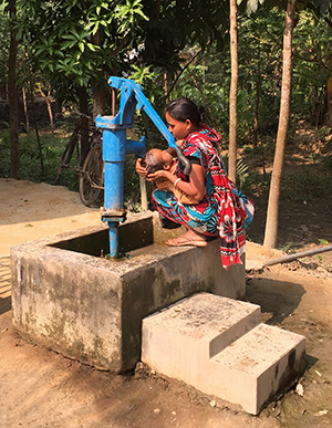 mother in Bangladesh washing baby at well