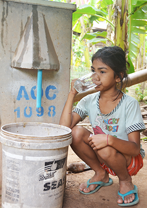 little girl in cambodia with bio sand filter